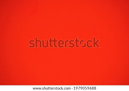 Monochrome surface of bright orange material with vignetting and gradient at the edges. Background, pattern, texture.