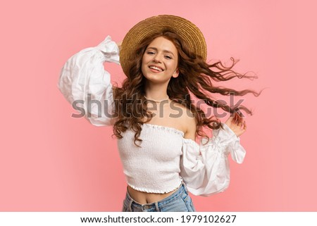 Laughing  red-haired white woman having fun  in studio on pink background. Perfect wavy hairs, straw har, white summer top with sleeves.