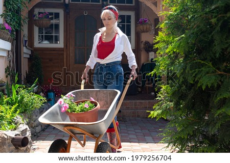 Beautiful blond middle aged woman in white shirt and blue jeans pushing a handcart with flower Royalty-Free Stock Photo #1979256704
