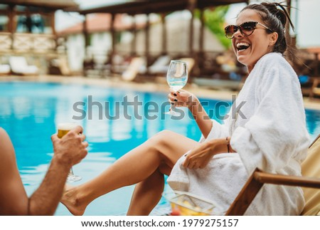 Portrait of a young smiling woman holding vine glass and chilling by the swimming pool on a deck chair with blurred background. Vacation concept stock photo. Happiness photos.