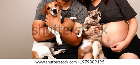 Taking fashion photo portrait of pregnant woman holding cat and her husband holding dog in concept of pets lover.