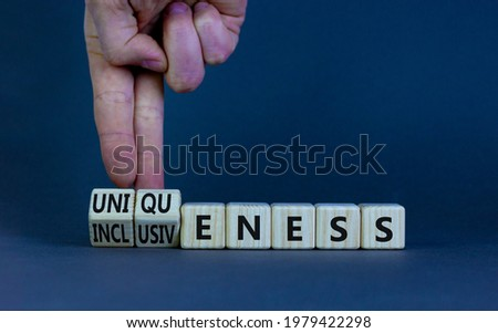 Inclusiveness and uniqueness symbol. Businessman turns wooden cubes, changes words inclusiveness to uniqueness. Beautiful grey background. Business, inclusiveness and uniqueness concept. Copy space.