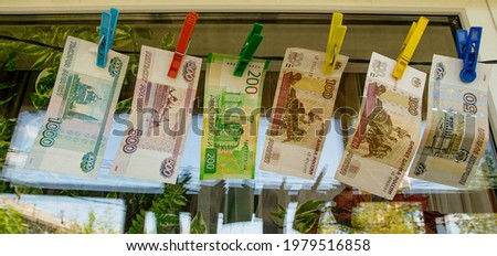 Russian paper banknotes of fifty, one hundred, two hundred, five hundred and one thousand rubles are attached with a clothespin to a clothesline for drying clothes Royalty-Free Stock Photo #1979516858
