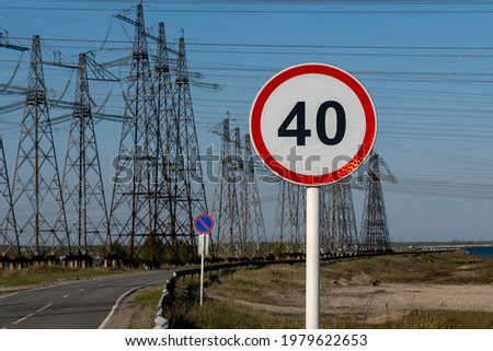 Road sign speed limit 40 km h against the background of the industrial landscape.