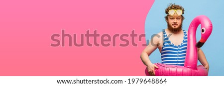 Funny red-headed man in swimming suit isolated on pink blue background.