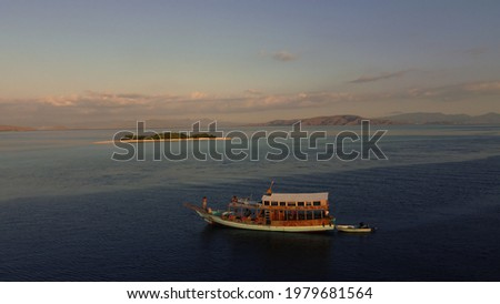 Drone shot of a wooden boat for sunrise sailing the Komodo islands while the guest are taking pictures of a small island. Scenic vacation landscape