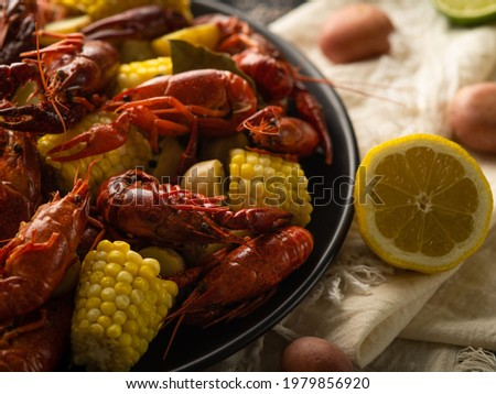 Pictured is a large black plate with boiled crayfish and corn. Half a lemon lies nearby. Light background. Bright colors. Close-up. Thorough review. Macro photography.