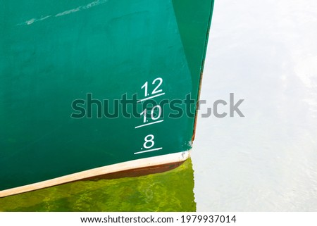 The bow of a large green, white, and red striped ship with water line numbers in meters from the boat reflecting on the water. There are 8, 10, and 12 in white letters on the green part of the ship