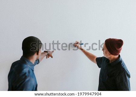 People writing on a white wall mockup Royalty-Free Stock Photo #1979947904