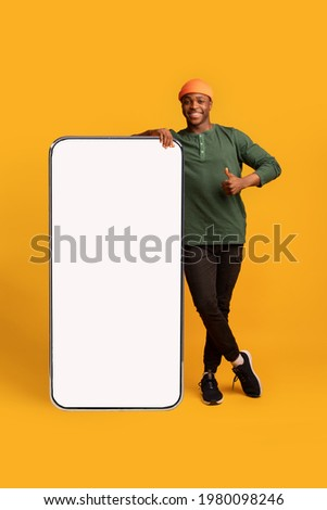 Happy Black Hipster Guy Leaning At Big Smartphone With Blank White Screen And Gesturing Thumb Up, Cheerful African Man Recommending New App Or Website, Standing On Yellow Background, Mockup Image Royalty-Free Stock Photo #1980098246