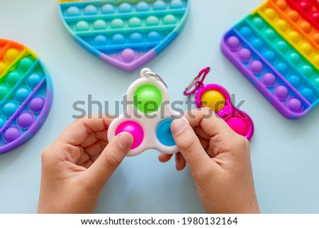 colorful trendy antistress sensory toy fidget push pop it and simple dimple in kid's hands on blue background Royalty-Free Stock Photo #1980132164