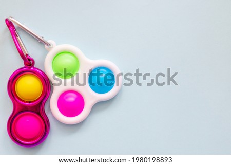 colorful antistress sensory toy fidget push simple dimple on blue background Royalty-Free Stock Photo #1980198893