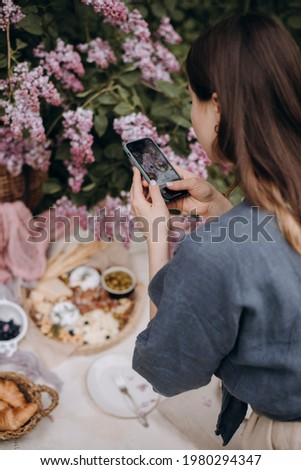girl makes a picnic photo on the phone. young brunette woman with wavy hair takes pictures on the phone in the park.