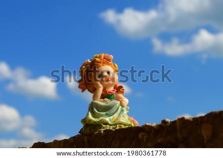Funny figurine. Angel girl on a background of blue sky.