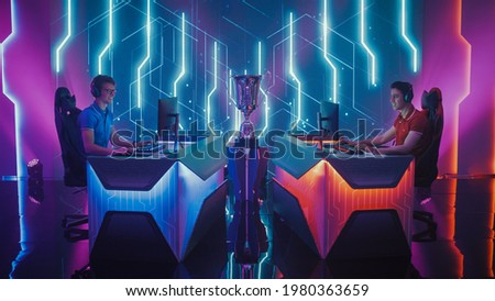 Two Professional Esport Gamers Competition in a Video Game on a Championship Arena, Both Playing Computer Games. Global Online Streaming Cyber Games Tournament Royalty-Free Stock Photo #1980363659
