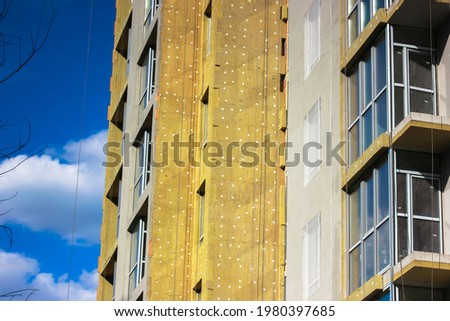 Warming of a multi-story residential building facade with a mineral wool, rock wool. External insulation of apartments, houses facades. Repair work on a construction object. Heat and sound insulation. Royalty-Free Stock Photo #1980397685