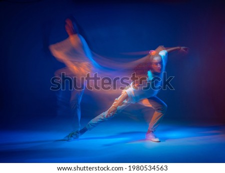 Mixed race female dancing in colorful neon light. Studio photo with long exposure. Expressive contemporary hip hop dance