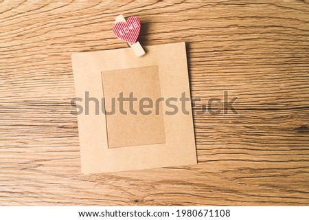 Old paper photo frames pace on wood background