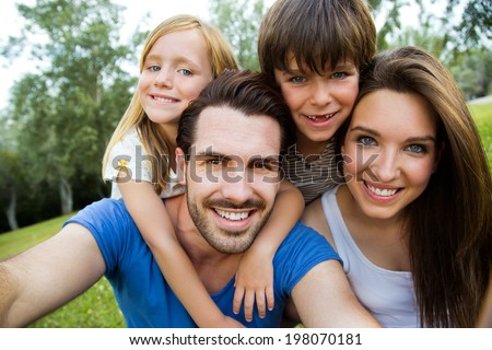 Summer scene of Happy young family taking selfies with her smartphone in the park