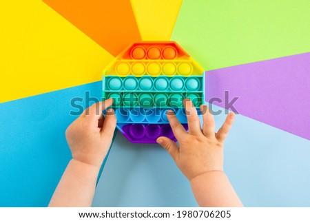 kids hands push sensory popit on colorfull background. Antistress pop it toy. Rainbow silicone sensory fidget New popular trendy silicone toy. Royalty-Free Stock Photo #1980706205