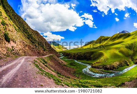 A stream in a beautiful green mountain valley. Green mountain hill valley river stream landscape. Beautiful mountain river valley landscape. River valley in mountain hills