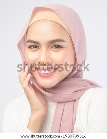 A portrait of young smiling muslim woman wearing a pink hijab over white background studio. Royalty-Free Stock Photo #1980739316