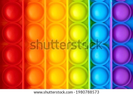 Colorful anti-stress fidget push pop it sensory toy for children close up. Simple dimple. Top view, flat lay. Royalty-Free Stock Photo #1980788573