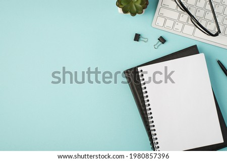 Top view photo of planners pen binders plant and glasses on keyboard on isolated pastel blue background with copyspace Royalty-Free Stock Photo #1980857396