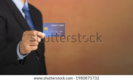 Businessman holding a mockup blue credit card while standing with a brown background. Close-up photo. Money and business concept.