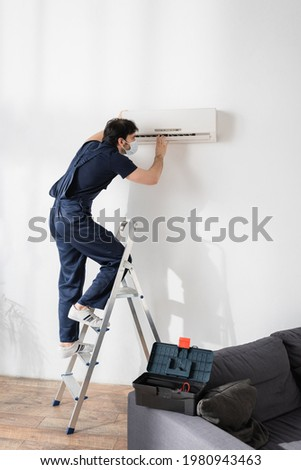repairman in medical mask standing on ladder and fixing air conditioner in living room Royalty-Free Stock Photo #1980943463