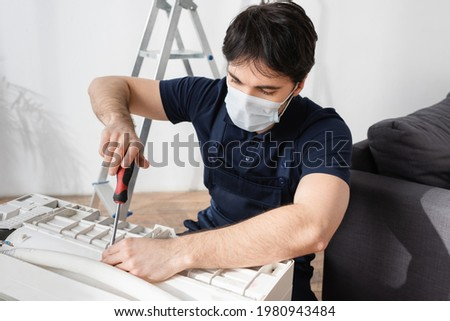 repairman in medical mask holding screwdriver and fixing broken air conditioner Royalty-Free Stock Photo #1980943484
