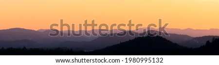 mountain layers after sunset during golden hour, orange sky, mountain silhouettes, sky during dusk Royalty-Free Stock Photo #1980995132
