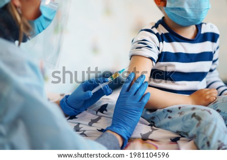 Childhood vaccination. Children's doctor vaccinating little boy at home. Vaccine for covid-19 coronavirus, flu, infectious diseases. Royalty-Free Stock Photo #1981104596