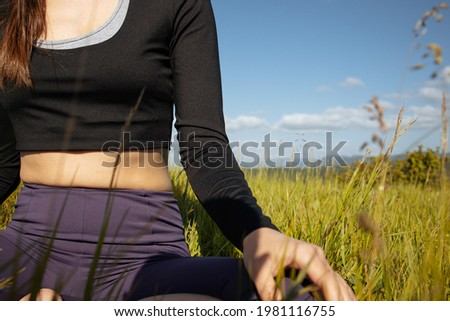 Close up picture of hands doing meditation.Young woman practices yoga in lotus position on an early sunny morning dew soft selective focus.