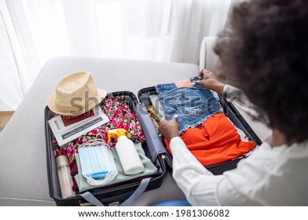 Travel during covid-19 pandemic. Upper view of modern woman with antiseptic, wheel bag, air tickets, medical mask, spf, bikini and covid passport packing wheel bag in the modern house in sunny day. Royalty-Free Stock Photo #1981306082