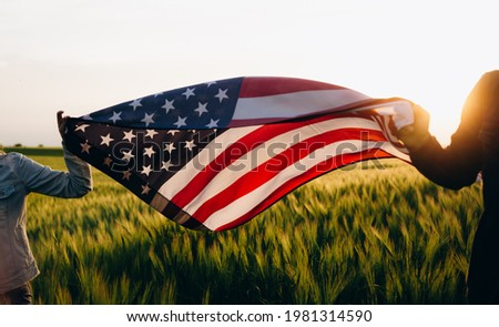 4th of july Patriotic holiday. Independence day. Hands holding american flag at sunse.  Royalty-Free Stock Photo #1981314590