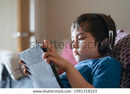 Child lying on couch wearing headphone listening to music, Close up face Kid sitting on sofa watching cartoons on tablet,Young boy playing game on touch pad or relaxing on his own in living room