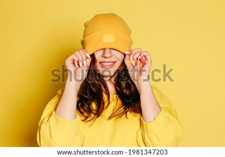Happy young female in trendy yellow sweatshirt and knitted hat covering eyes smiling brightly against yellow background Royalty-Free Stock Photo #1981347203