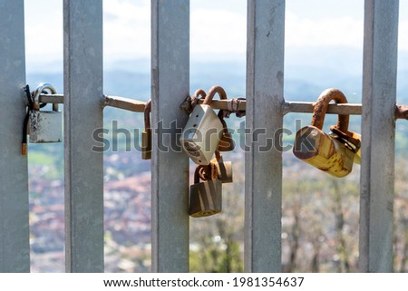 Old rusty closed padlocks on a metal fence. A symbol of love and romance forever. Valentine's day idea. On a background of the sky and nature in blur