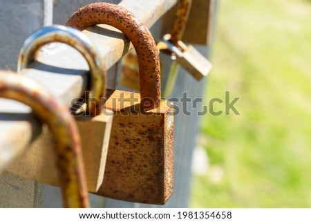 Old rusty iron closed padlocks on a metal fence. A symbol of love and romance forever. Valentine's day idea. Outdoors