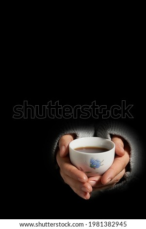 Cropped highlighted shot in darkness: woman in gray coarse pullover is warming her hands on little cup with black tea. White ceramic bowl is decorated with picture of butterfly and lotus flower.