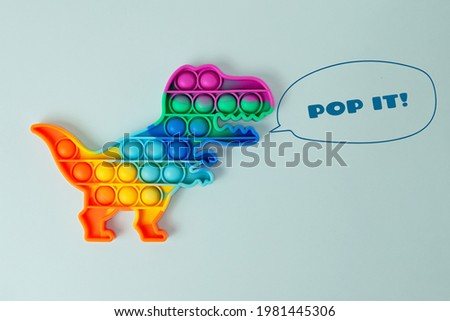 New silcone toy pop it in shape of dinosaur on the blue background,with drawing growls.New sensory antistress toy for children and adult.Trendy rainbow coloring. Royalty-Free Stock Photo #1981445306