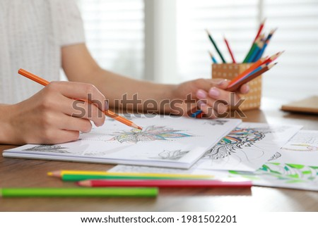 Young woman coloring antistress page at table indoors, closeup Royalty-Free Stock Photo #1981502201