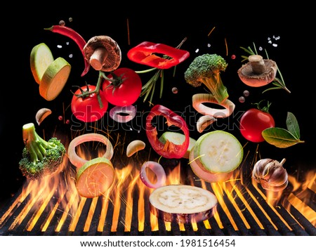 Grilled vegetables and mushrooms in motion falling down on open grill. Conceptual photo of barbeque cooking process.