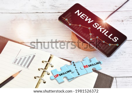 New skills technology on smart phone screen with growth graph on wireless charger with reskilling, up skilling and skills written on blue puzzle. Artificial intelligence machine learning concept Royalty-Free Stock Photo #1981526372