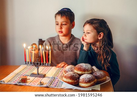 Brother and sister siblings lighting candles on menorah for Jewish Hanukkah holiday at home. Children celebrating Chanukah festival of lights. Dreidel and Sufganiyot donuts in plate on table.