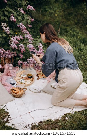 girl blogger takes photos or videos of outdoor picnic on her smartphone. girl in linen clothes photographs picnic setting. girl photographs food and snacks for a picnic on her phone.