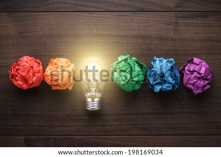 great idea concept with crumpled colorful paper and light bulb on wooden table Royalty-Free Stock Photo #198169034