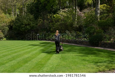 Blonde Female Gardener Mowing a Lawn with Diagonal Stripes on a Bright Sunny Day in a Garden in Rural Devon, England, UK Royalty-Free Stock Photo #1981781546