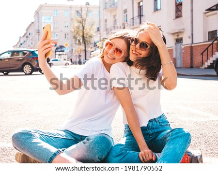 Two young beautiful smiling hipster female in trendy summer white t-shirt clothes and jeans.Sexy carefree women sitting on the street background. Positive models having fun, taking selfie photos